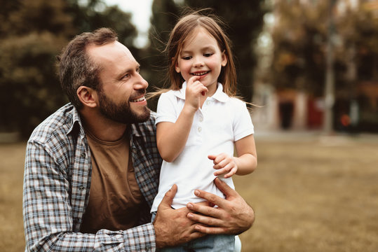 Side view of delighted man squatting near small kid and holding her. Little girl is standing with smile and enjoying leisure outdoors
