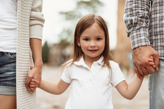 Waist up portrait of small smiling girl standing and holding mother and father hands. She is happy to spend time with dearest together