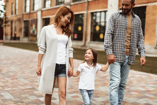 Full length of smiling mother and father walking on street with child. Small girl is holding their hands while looking at mom with joy