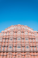 Vertical view of Hawa Mahal (Palace of Winds or Palace of the Breeze) with blue sky in background. Located on the edge of City Palace, Jaipur, Rajasthan, India