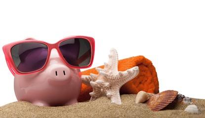 Piggy Bank with Sunglasses, Towel and Seashells on Sand