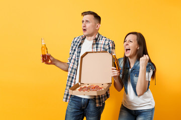Young couple woman man sport fans cheer up support team hold beer bottles italian pizza in cardboard flatbox do winner gesture screaming isolated on yellow background. Sport family leisure lifestyle.