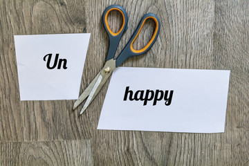 Unhappy Concept with Scissors Cutting  off the Word Un of Unhappy