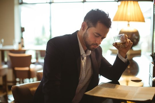 Businessman reading newspaper while drinking whisky