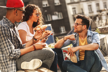 Group of friends hangout at the street.They eat pizza and drinking cold juice.Fast food.