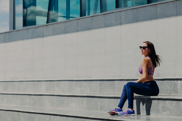 Horizontal shot of young female being in good shape, sits at stair, wears shades, top, trousers and sneakers, breathes fresh air, takes break after long training or jogging. Training in open air