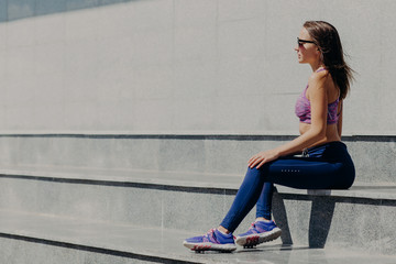 Athletic female in sports clothes, rests after running in open air, wears sunglasses, sits on stairs outdoor with copy space for your advertisement or promotional text. People and sport concept