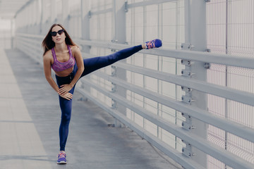 Portrait of sporty female does workout yoga exercise and stretching, has muscular body, wears sunglasses, sportshoes and clothes, prepares for sport competition. People and flexibility concept