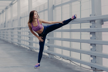 Sport, training, fitness and lifestyle concept. Young woman with slender legs, stretches muscles before running exercise, poses outdoor, shows her nice flexibility, dressed in sportsclothes.