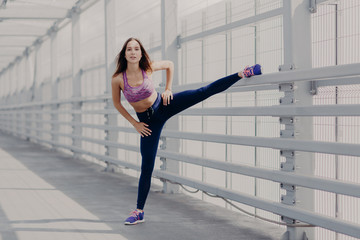 Healthy young fitness female in sportswear does outdoor workout and stretching exercise, wears sport shoes, being famous athlete, has healthy lifestyle. People, sport, lifestyle and health concept