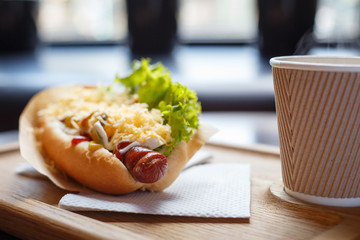 Hot dog with salad and cup of coffee on the table in cafe
