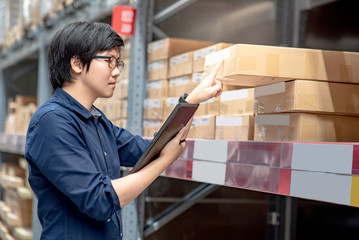 Young Asian man doing stocktaking of product in cardboard box on shelves in warehouse by using digital tablet. physical inventory count concept
