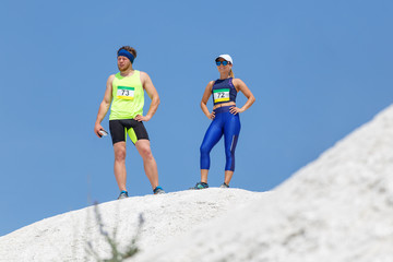 Man and woman standing on the hill before start of running race against blue sky