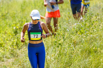 Young slim woman running trail race contest.