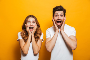 Image of young people man and woman in basic clothing screaming in surprise or delight and touching cheeks, isolated over yellow background
