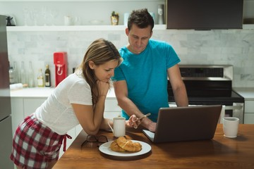 Couple using laptop and mobile phone in kitchen