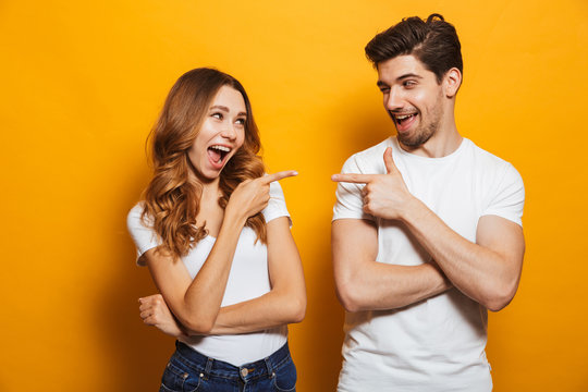 Image of happy young people man and woman in basic clothing laughing and pointing fingers at each other, isolated over yellow background