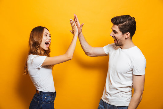 Image of friendly young people man and woman in basic clothing laughing and giving high five, isolated over yellow background