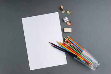 Color pencils on a gray background with a white sheet ready for drawing