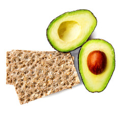 Isolated avocado fruit. Two halves of avocadoes with wholegrain crispy bread  isolated on white background. Healthy breakfast with Crispbread