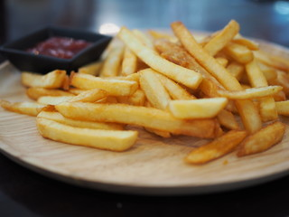 Fresh fried french fries with ketchup on wooden dish