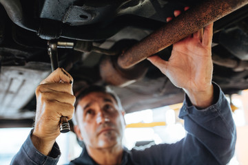 Auto mechanic repairing a car in service station