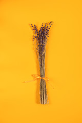 Beautiful dried lavender bouquet on yellow surface