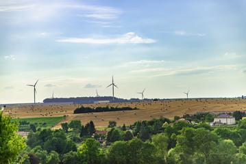 Vue sur les champs et une ferme agricole à la campagne en été en Moselle avec des éoliennes sur l'horizon