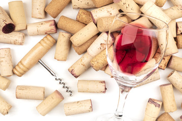 Glass of red wine with corks and corkscrew on a white background