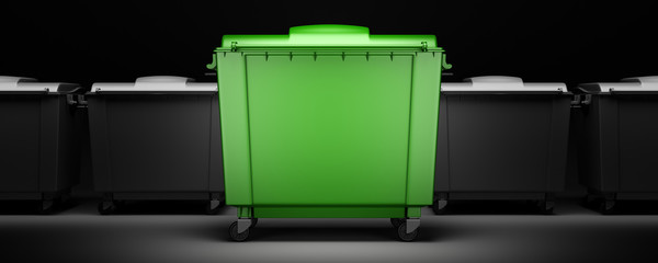 green garbage container among gray containers isolated on dark background