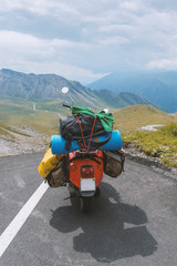 Individual travelling concept: vintage scooter with a lot of luggage parking on top of a mountain in the alps