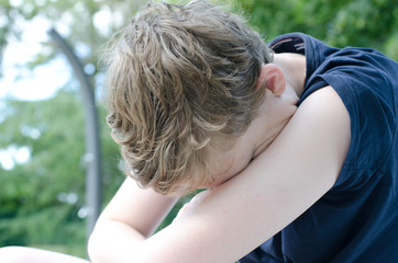 Teenage boy with head in arms