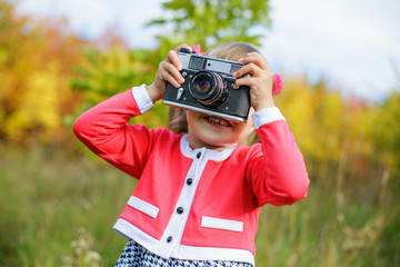 a little girl in a pink jacket and a black and white dress with two tails photographing an old camera