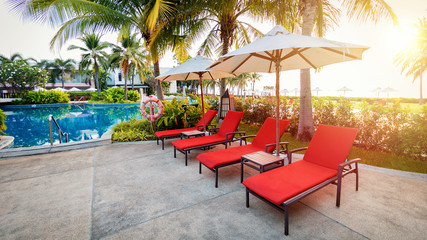 Red sun chairs at the pool in the morning time or sunrise time