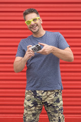 Portrait of hipster guy holding vintage camera on red background.