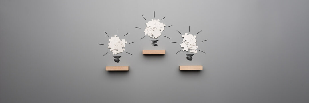 Wide panorama view of three light bulb formed by white puzzle pieces placed on wooden pegs
