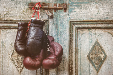 Two pair of vintage boxing gloves hanging on a weathered ancient door