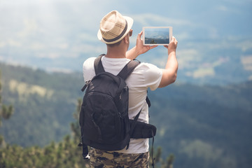 Young traveler with backpack taking photos of beautiful landscape
