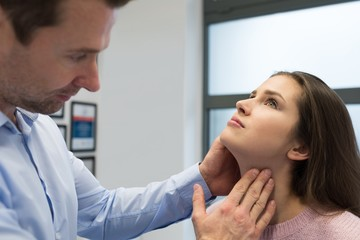 Physiotherapist giving neck massage to woman
