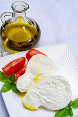 Fresh soft Italian white cheese mozzarella buffalo, original from Campania, Paestrum and Foggia regions, South Italy, served with tomatoes, fresh basil and olive oil