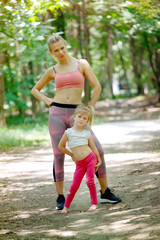 Woman and little girl posing in park after training. Family exercise, healthy lifestyle