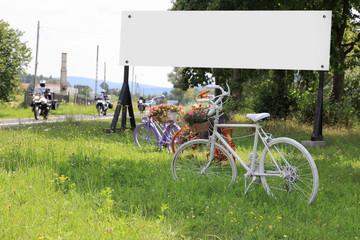Kwietniki na rowerach, bilbort reklamowy i motocykliści.