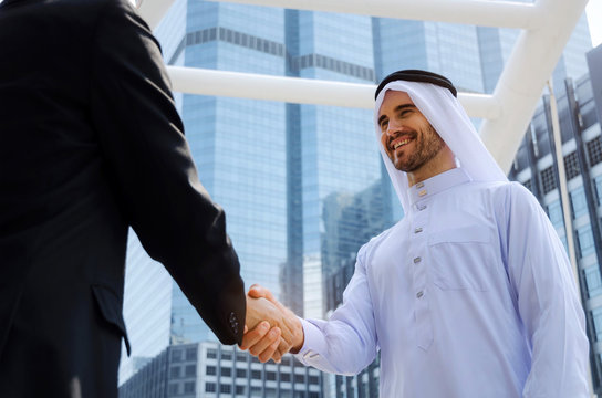 Deal. young handsome Arabian man in white suit handshake with asian business man in black suit after finishing up meeting, partnership, teamwork, community, connection financial and investment concept