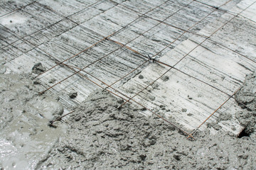 The wet concrete is poured on wire mesh steel reinforcement