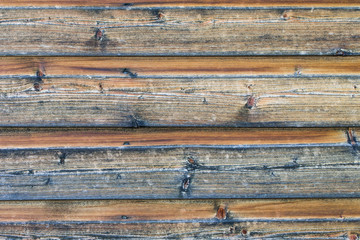 Brown-golden weathered wood cladding of a house wall