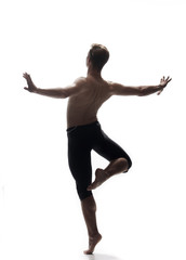 rear view, one young man back, ballet dancer, posing arms outstretched, standing on one leg in air, white background, photo shoot.