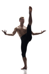 front view, one young man, ballet dancer, standing on one leg, other leg in high in mid-air, white background. arms outstretched.