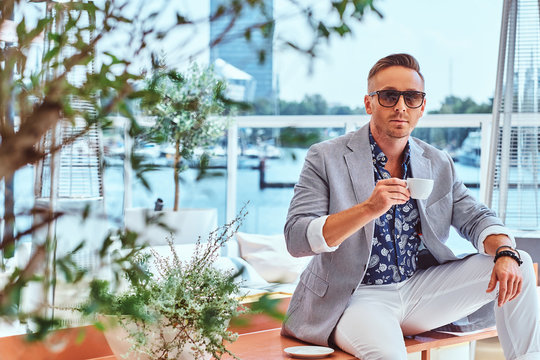 Confident successful man with stylish hair dressed in modern elegant clothes holds cup of coffee while sitting on a table at outdoor cafe against the background of city wharf.
