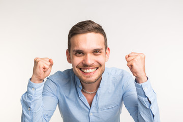 Emotions and people concep t- young happy man raised his fists up over the white background