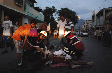 Red Cross paramedics attend to an injured man shot in a drive-by shooting as residents react in Monterrey